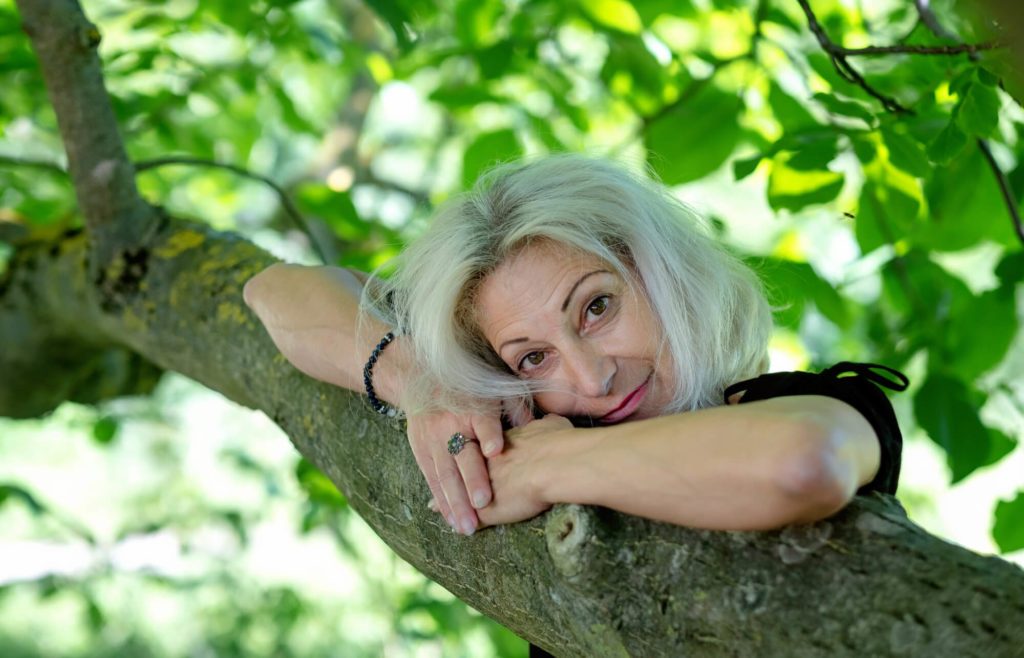 Senior woman 60 plus in a tree